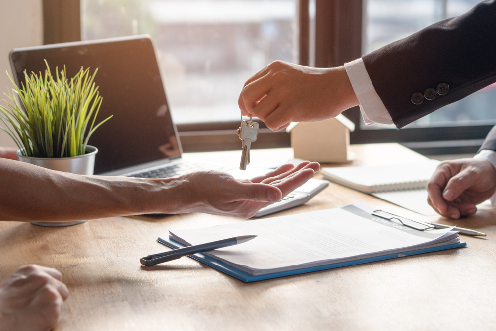 Estate agent handing keys to lease